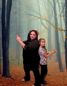 Mum and daughter back to back in a forrest