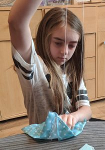 Girl sewing a dog bandanna