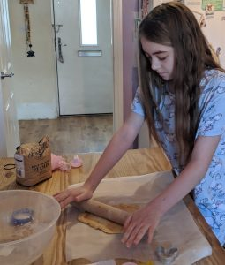 Girl rolling out the dough for homemade dog treats