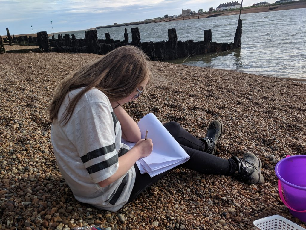 A girl sitting on the beach sketching