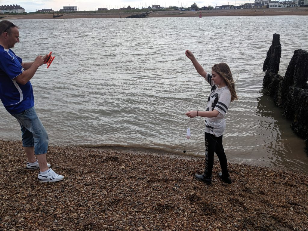 Man with his daughter crabbing on the Suffolk coast