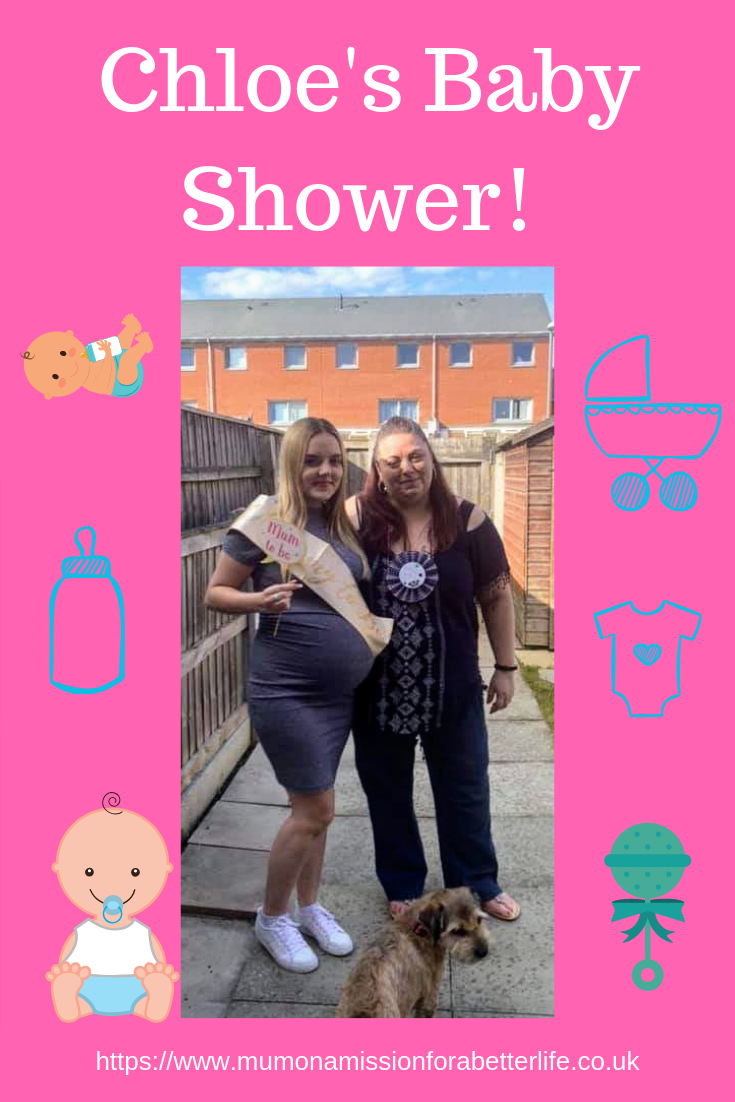 Woman and her pregnant daughter in the garden at a baby shower with baby related decorations around the main picture