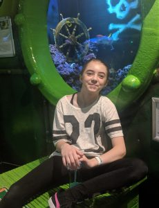 Young girl sitting in front of a port hole in an aquarium.