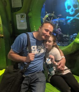 Dad and daughter sitting together in a sea life centre