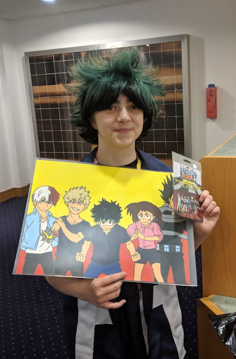 Girl wearing black and green spikey wig holding a painting of cathers from my hero academia anime