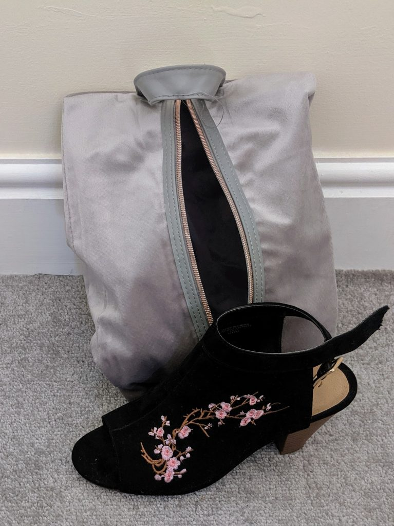 Shoe bag with one of the shoes on display. The shoe is a black open toe heel with embroidered flowers on the front