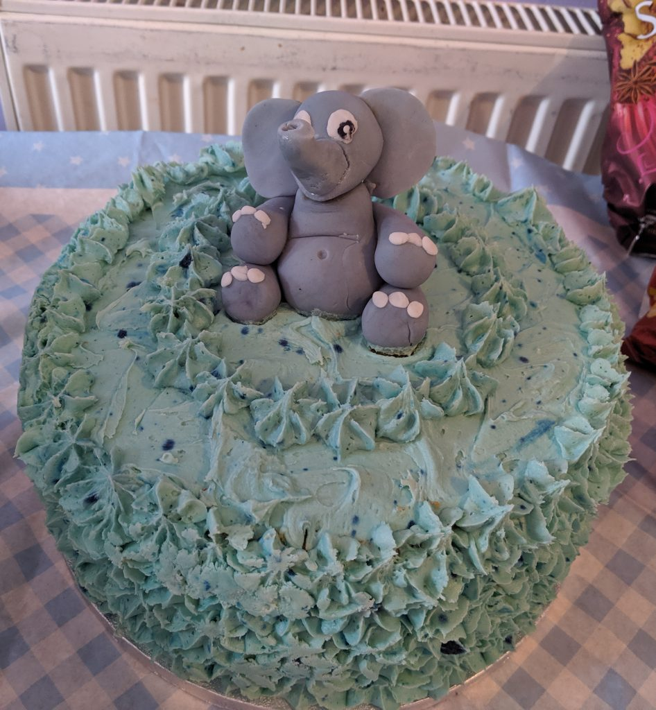 Large aqua blue iced baby shower cake with a edible elephant decoration on the top