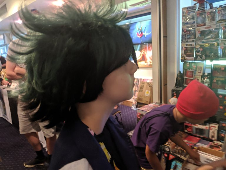 Side view of a girls face who is wearing a black and green spiky wig at comic-con
