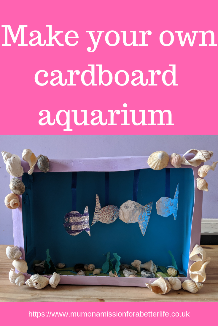 A cardboard box painted purple and decorated with sea shells with foil fish hanging to make an aquarium