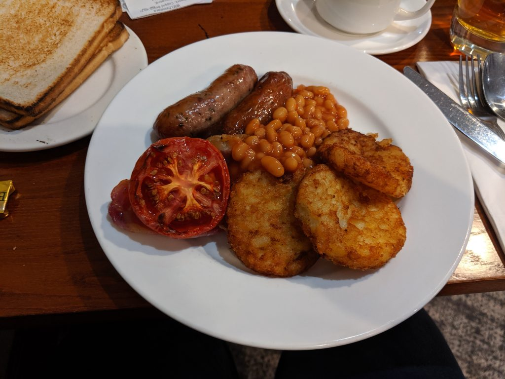 A close up of a full English breakfast at a blogging conference - sausages, hash browns, beans and a grilled tomato