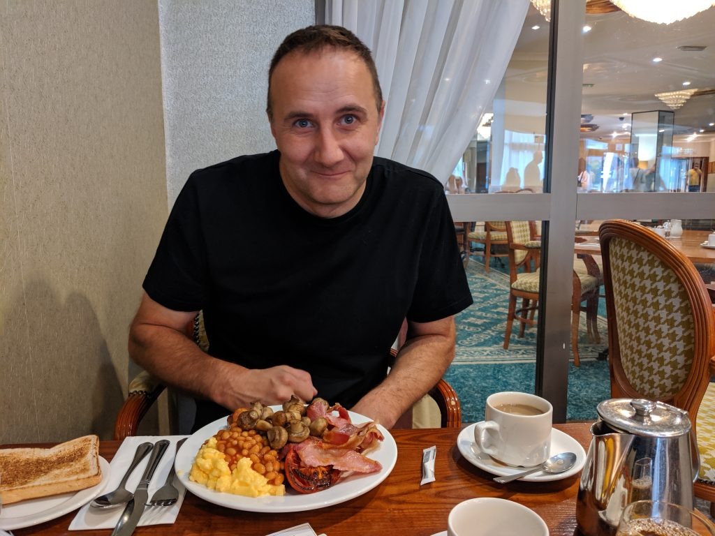 A man sitting at a table with a big fried breakfast in front of him at a blogging conference