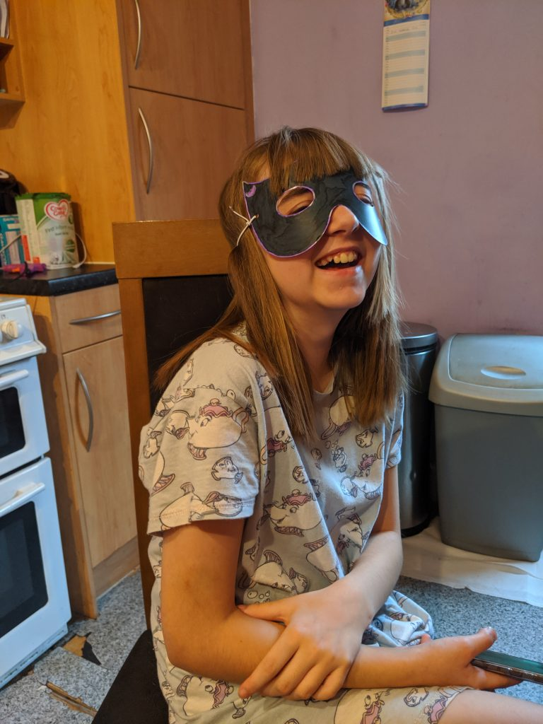 Faith wearing her finished mask with a huge smile on her face