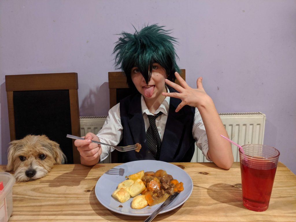 Girl in cosplay at the dinner table sitting next to a dog.
