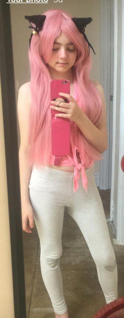 Girl in light gray leggins, a pink top, long pink wig and black cat ears