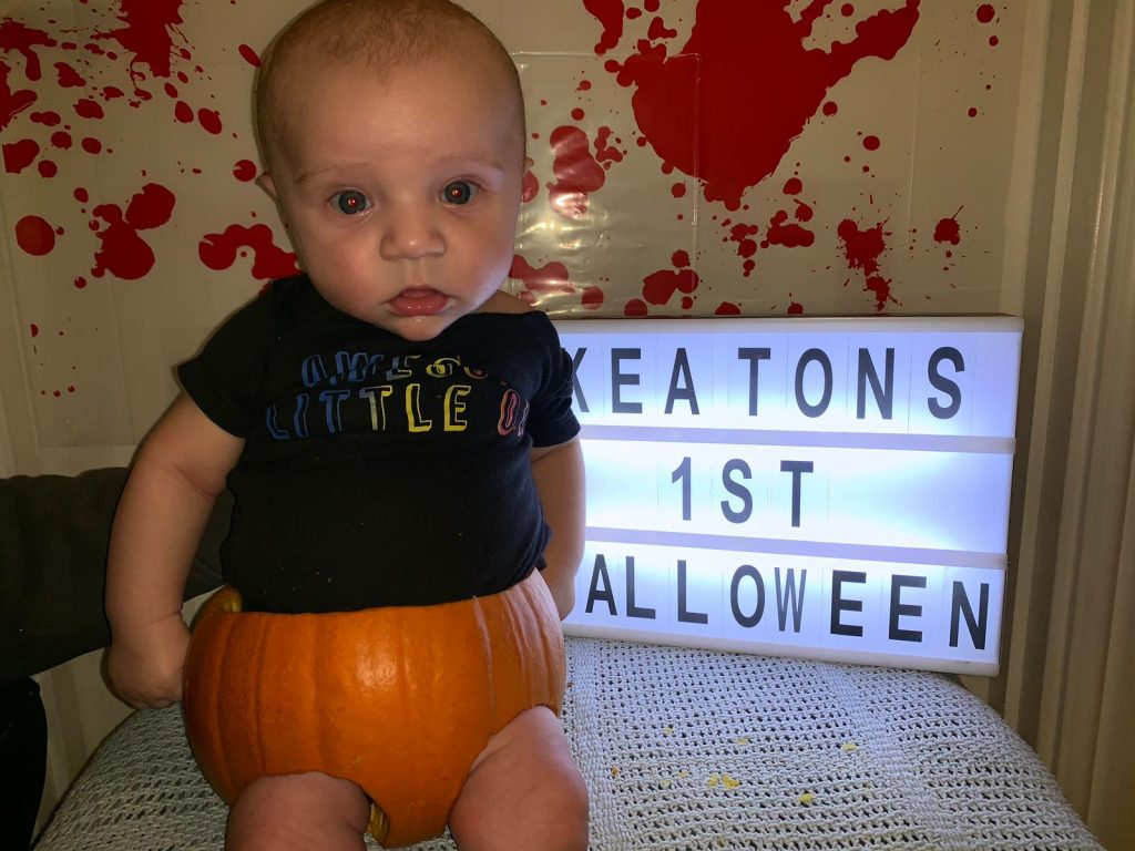 Baby sitting in a pumpkin with a light sign saying 'Keatons 1st Halloween'