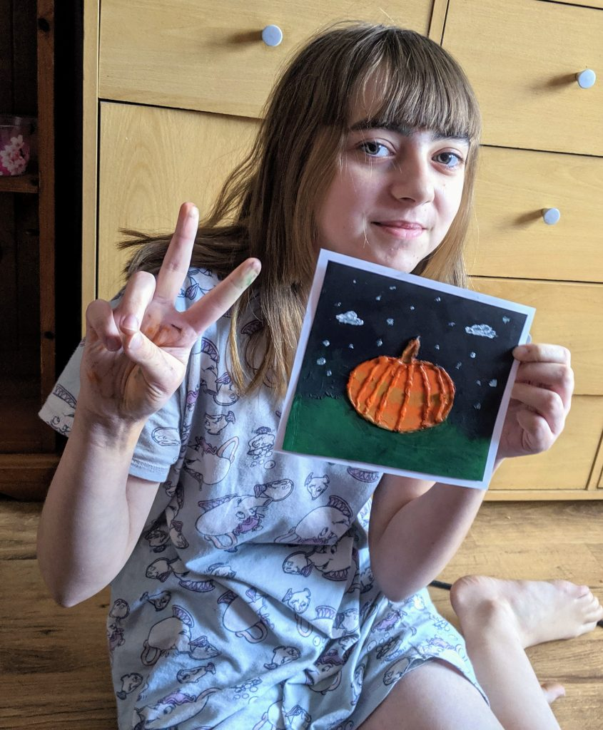 Faith showing her artwork - A glue resist pumpkin picture