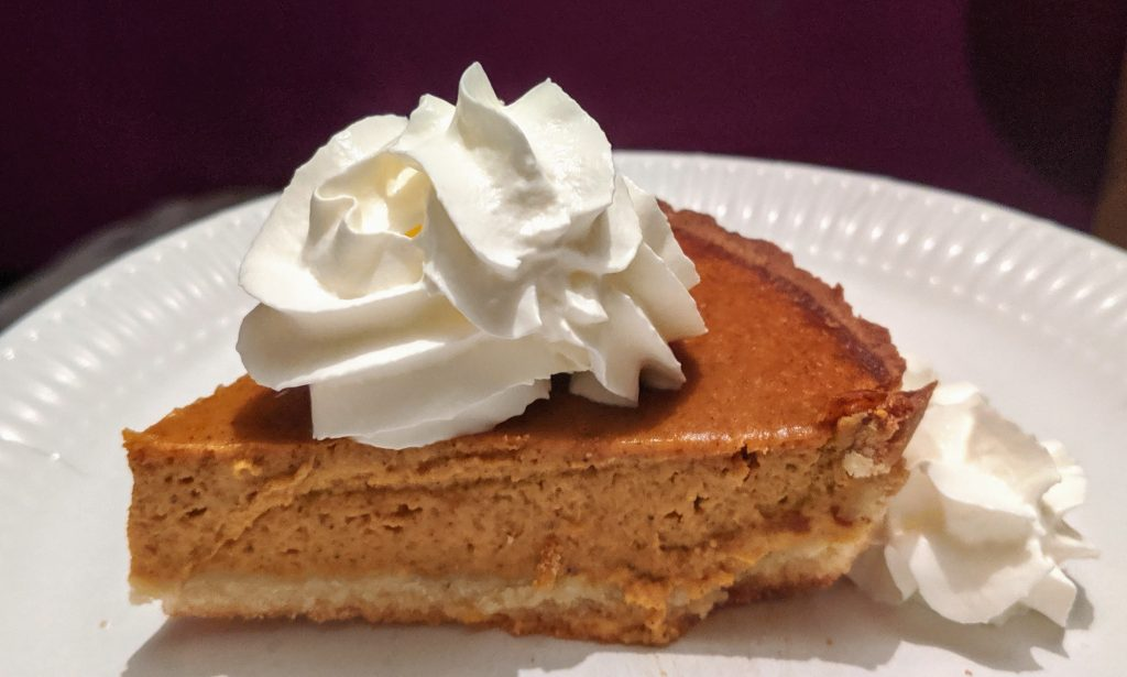 A slice of pumpkin pie with a squirt of cream on top