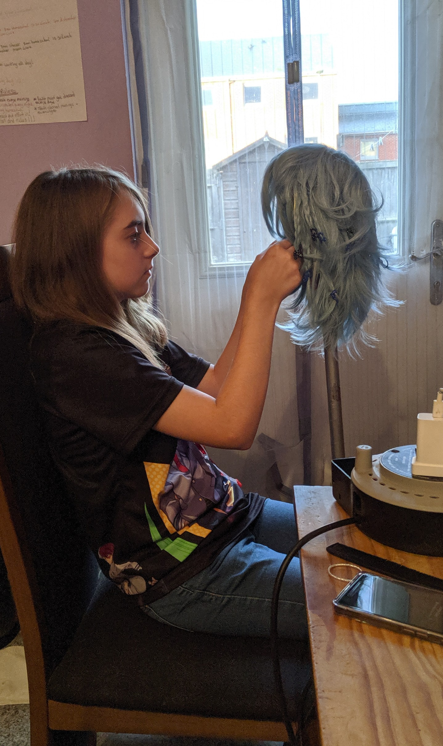 Faith styling her wig at the kitchen table