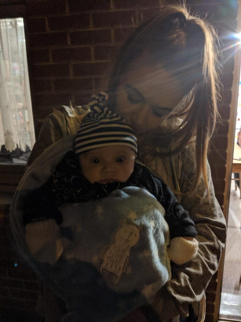 Lauren holding baby K outside at night