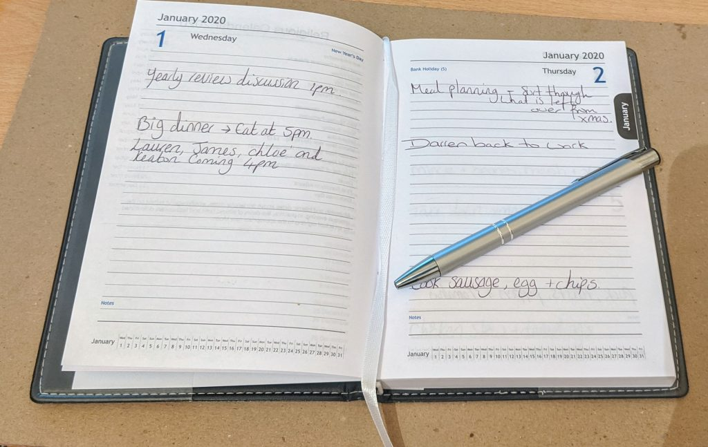 Inside the black page a day planner and a silver ballpoint pen