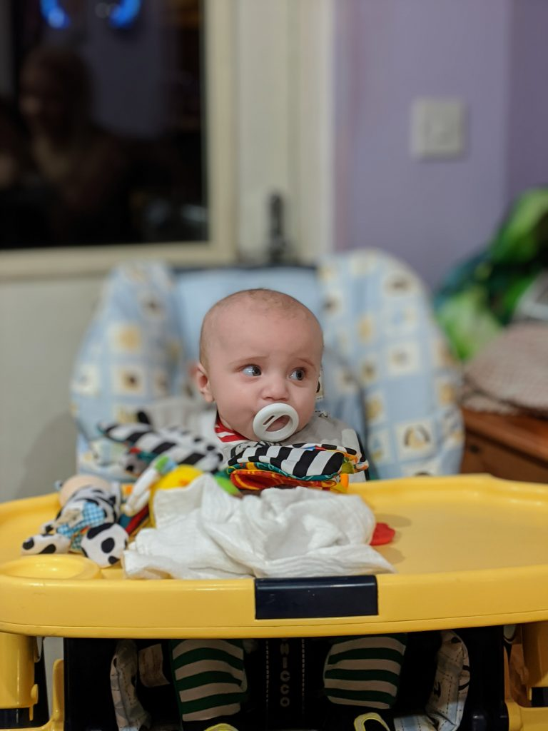 Baby boy in high chair with dummy in mouth