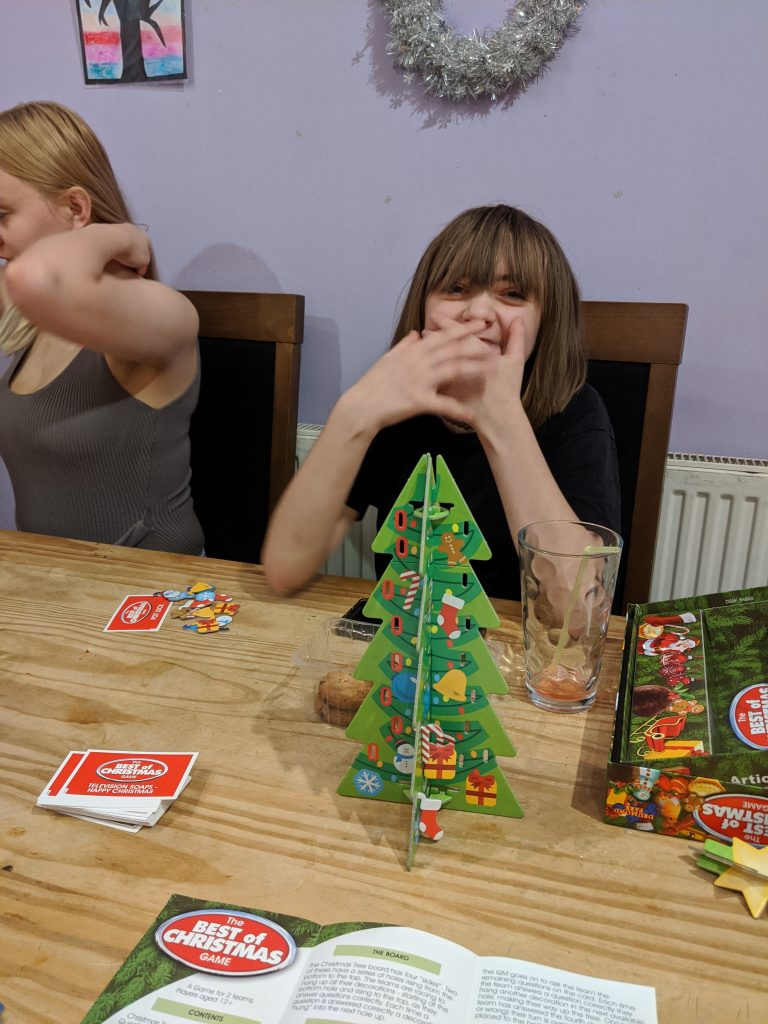 Faith at the table with a Christmas tree board game in the middle f the table