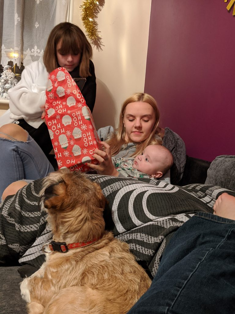 Chloe holding baby opening a Christmas present with faith in the background
