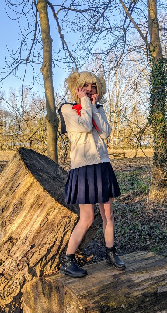 Faith in cosplay standing on a log in the woods
