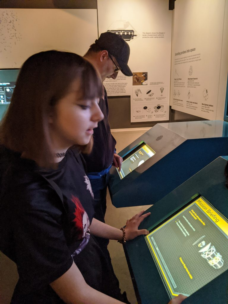 Faith and Darren playing the touchscreen game in the astronomy center