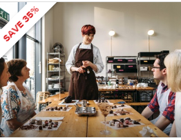 People sitting at a table being taught by a chef to make chocolates