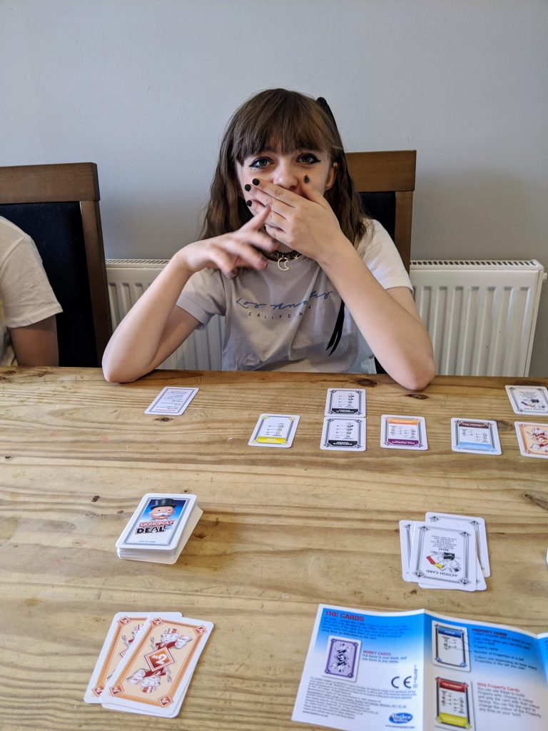 Girl sitting at table playing the card game monopoly deal