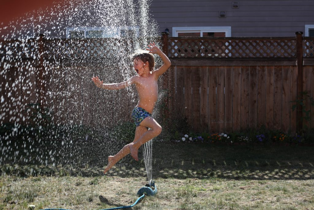 A boy jumping through a water sprinkler in his garden on a sunny day