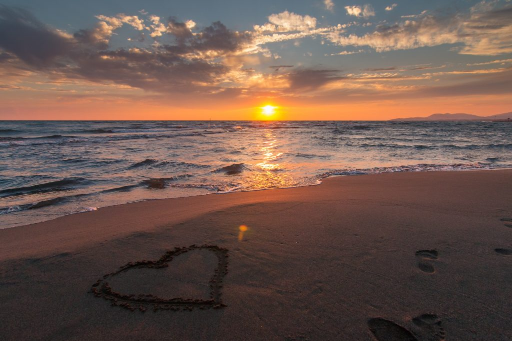 Sunset at the beach with a heart drawn in the sand