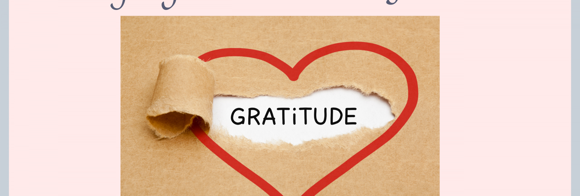 A red heart drawn onto brown paper with a piece ripped showing the word gratitude