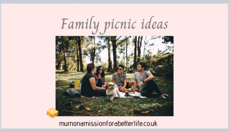 Four people and a dog enjoying a picnic in the park