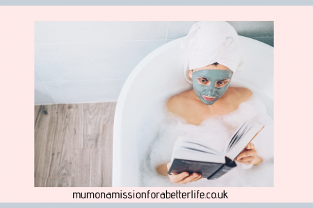Lady relaxing in a bath with a face mask on and a towel on her head reading a book in her home spa