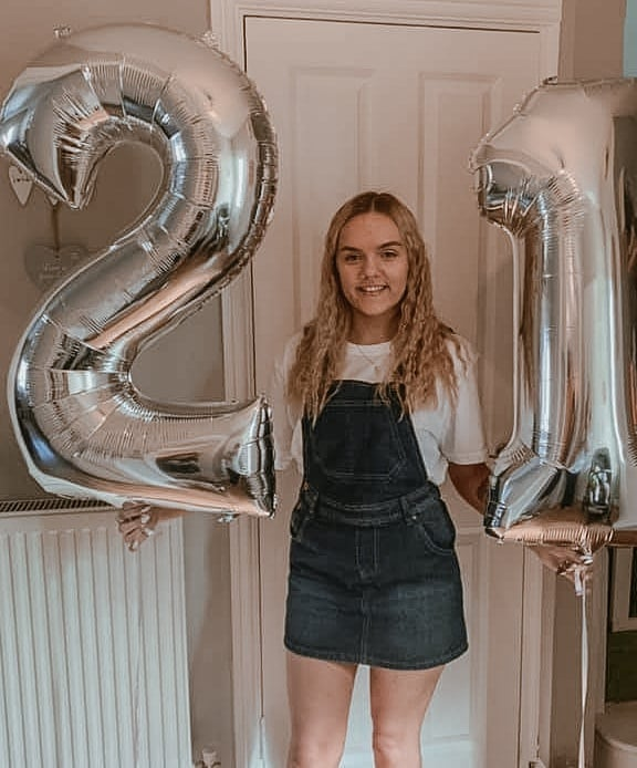 Chloe holding a 2 and 1 silver helium balloons.