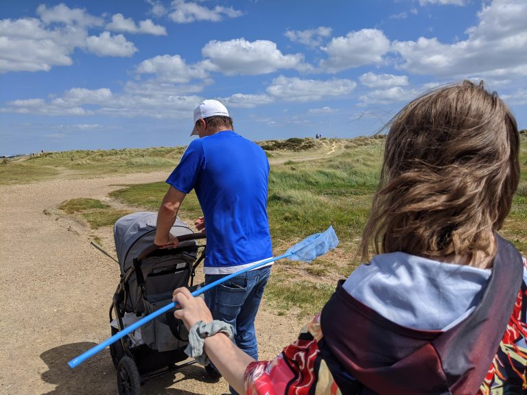 Darren pushing Keaton in the pushchair along Walberswick beach