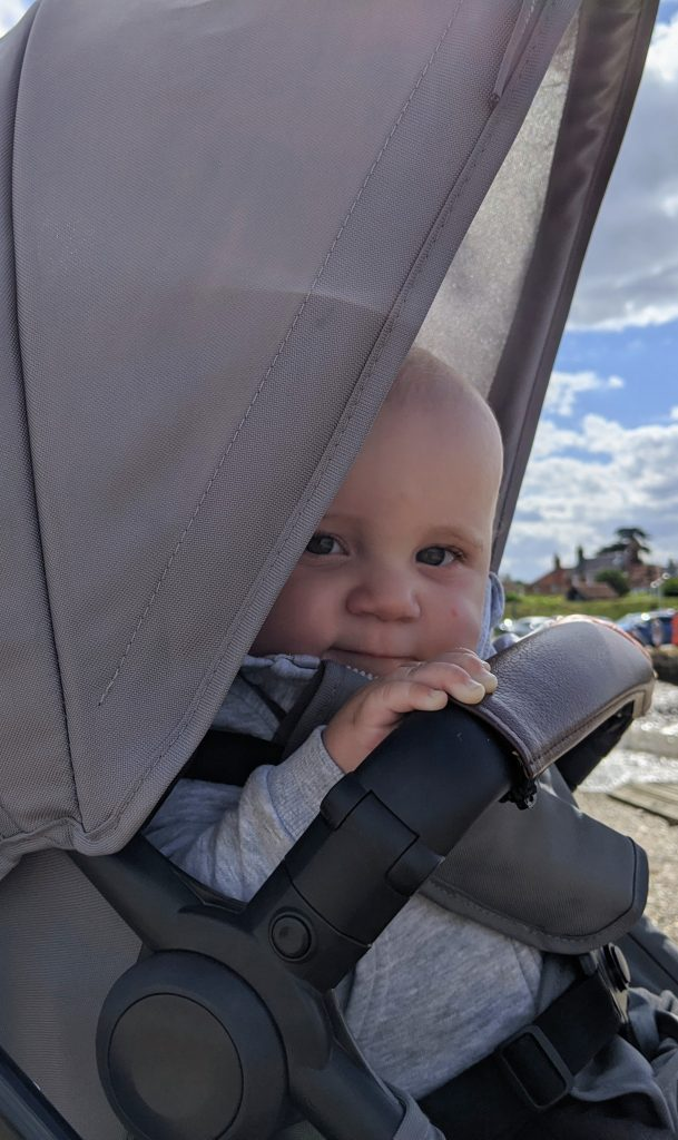 keaton. baby boy, sitting in pushchair smiling