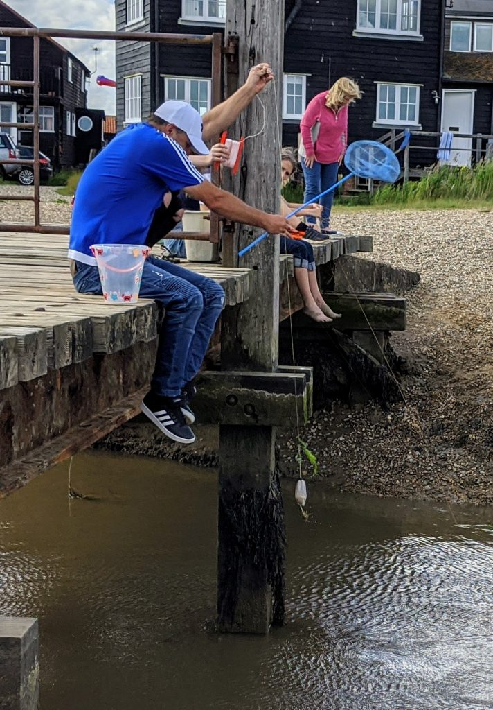 Darren and Faith on the bridge pulling in their crabbing line