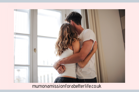 man and woman in each others arms looking out of a window. Relationships