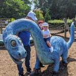 Keaton sitting on a blue dinosaur at roarr with Darren and Faith