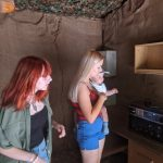 Chloe, Faith and Keaton in a cabin looking at a radio