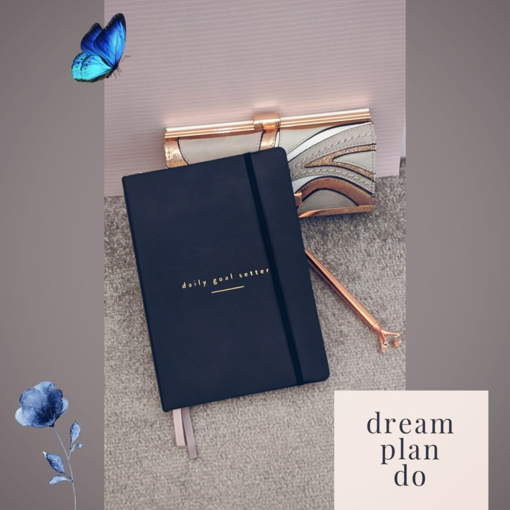 The goal setter planner with a rose gold pen and a rose gold and white purse in the background.
