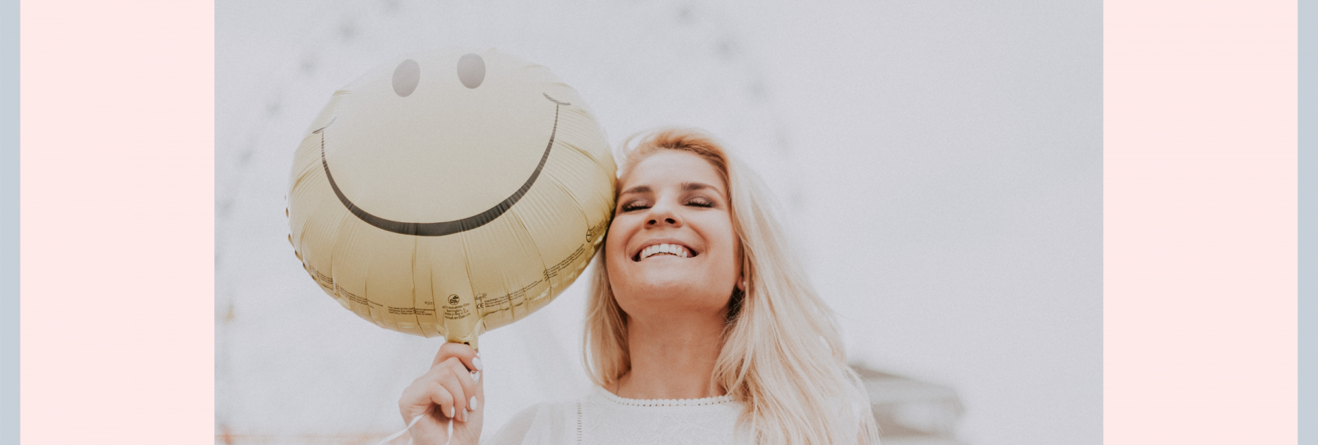Happy woman holding a yellow smiley balloon