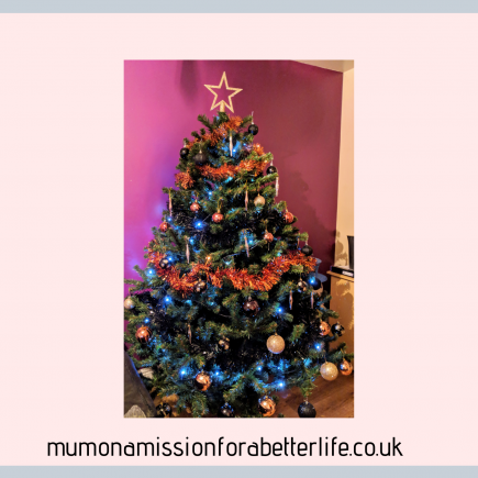 Christmas tree decorated in gold, black and bronze with blue lights