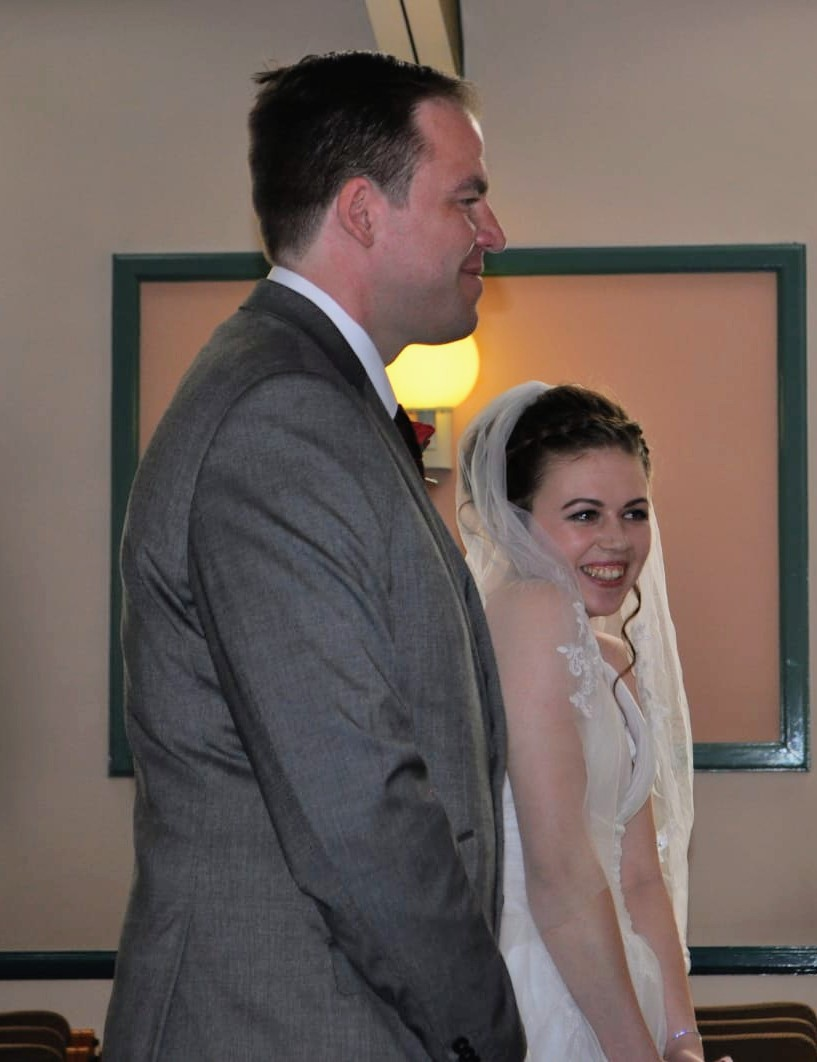 Man and young woman standing in a registry office at their COVID wedding about to say their vows.