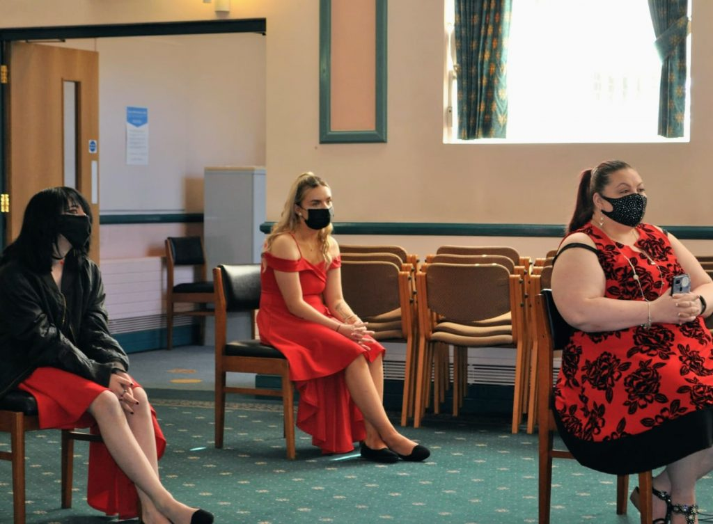 Mother of the bride and two bridesmaids all wearing red seated at a COVID wedding