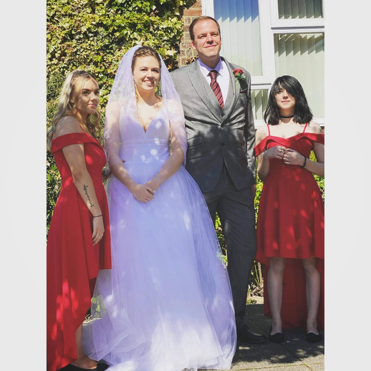 Bride and groom with a bridesmaid each side in red dresses at a COVID wedding