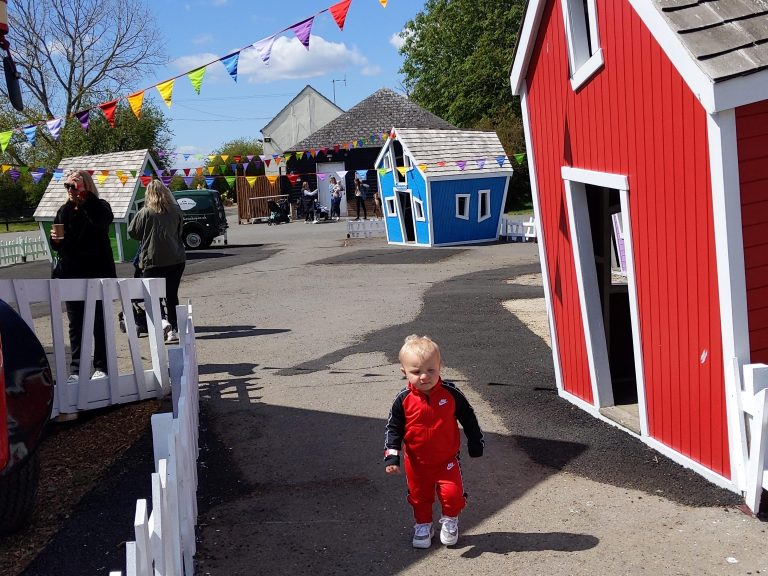 Keaton (male toddler) walking through the brightly painted wooden houses at Marsh Farm